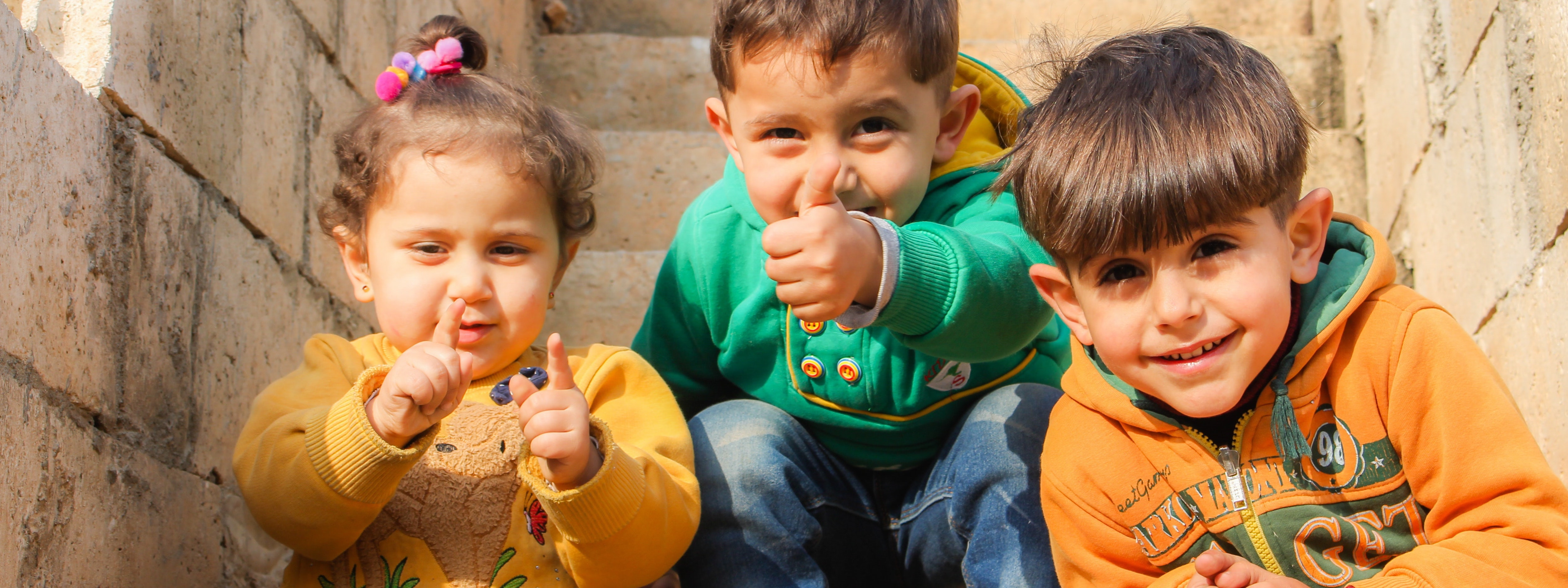 Background picture featuring 3 children with happy faces. A stock image obtained from  				https://www.pexels.com, photographed by	Samer Daboul.